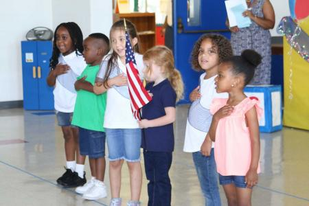 Children standing for the Pledge of Allegiance