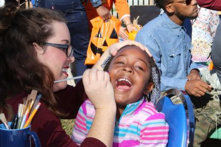 Child is having her face painted at the Fall Festival