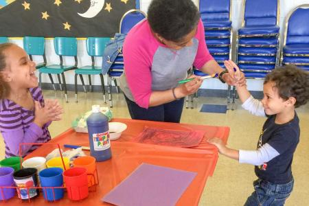 Children painting hand prints on Work Together Wednesday